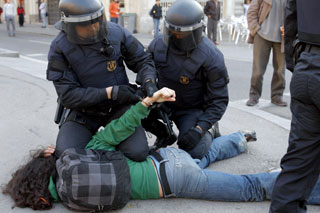 Dos agentes reducen a uno de los manifestantes (Efe).
