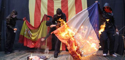 Unos encapuchados queman las banderas de España y Francia (Efe).